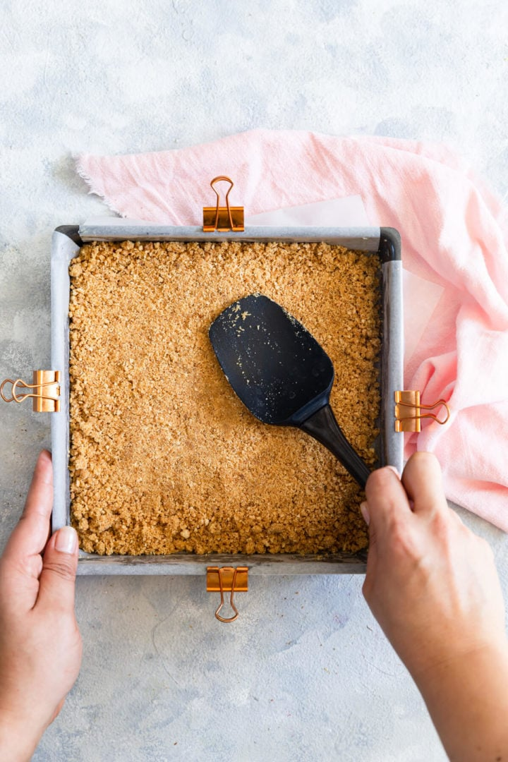 top view of a person pressing biscuit base into baking tin with spatula