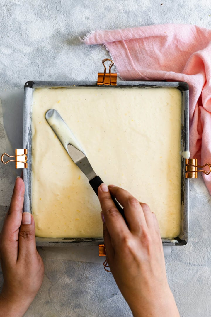 top view of a person smoothing the batter in a baking tin