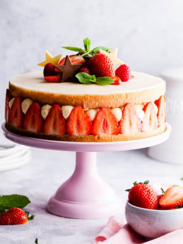 side angle close up of a strawberry cake on a pink cake stand