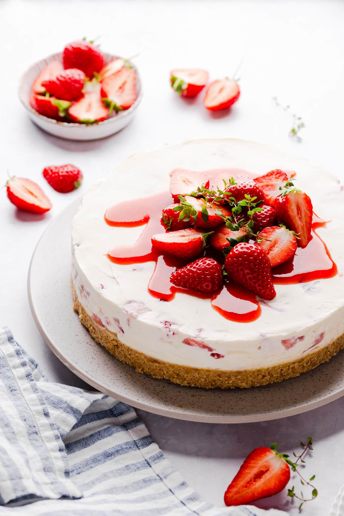 side angle view of strawberry white chocolate cheesecake topped with fresh strawberries and sauce