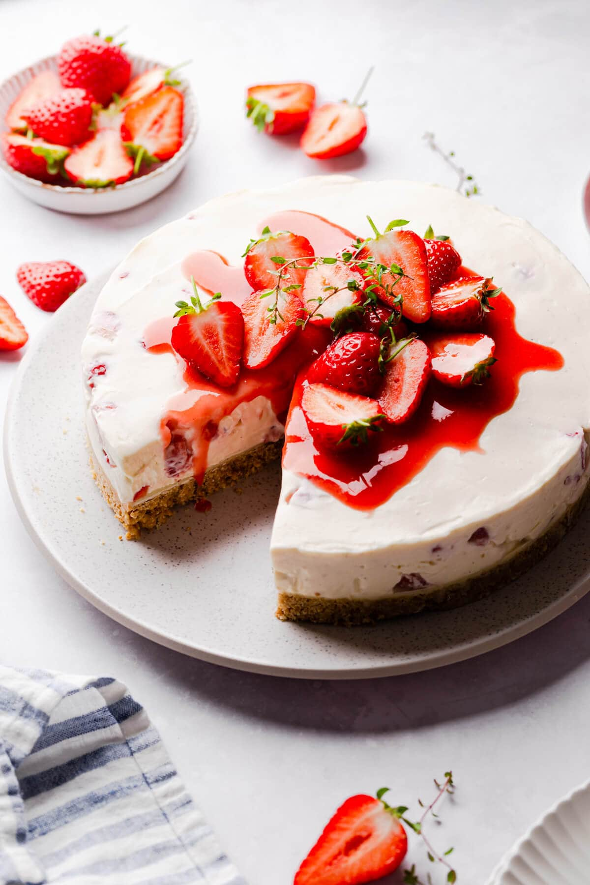 45 degree angle view of a strawberry cheesecake topped with strawberry sauce