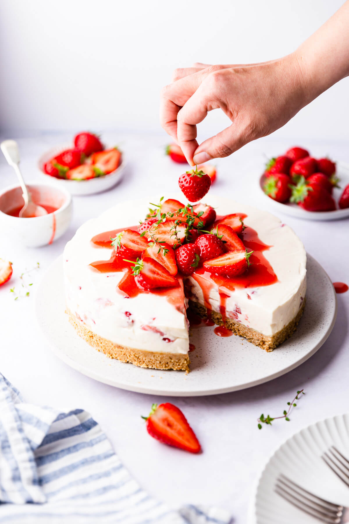 side angle of strawberry cheesecake being topped with fresh strawberry