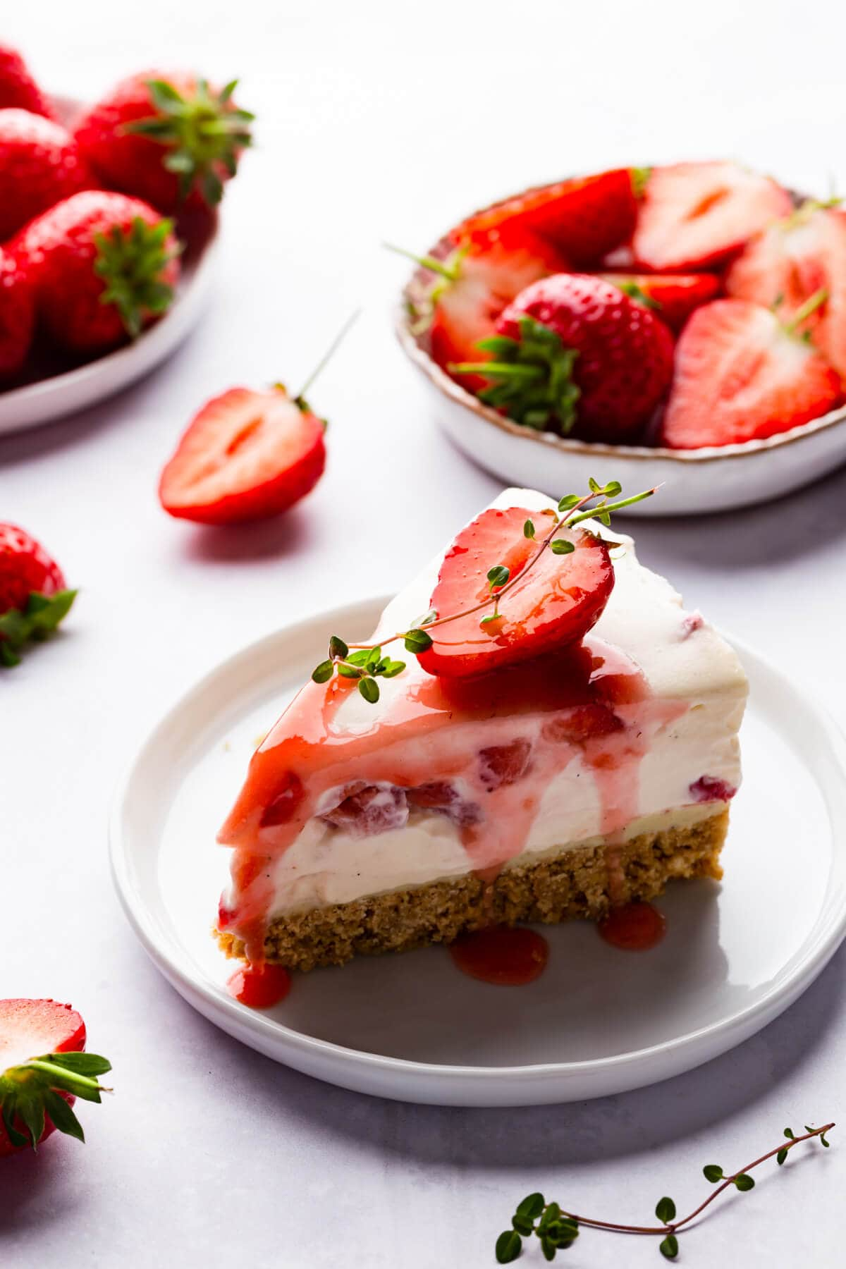 45 degree view of a single slice of strawberry white chocolate cheesecake on a small plate