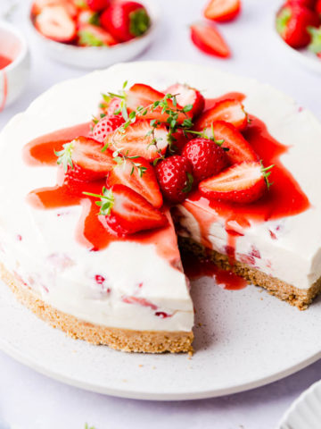 45 degree angle view of strawberry white chocolate cheesecake with a slice cut out
