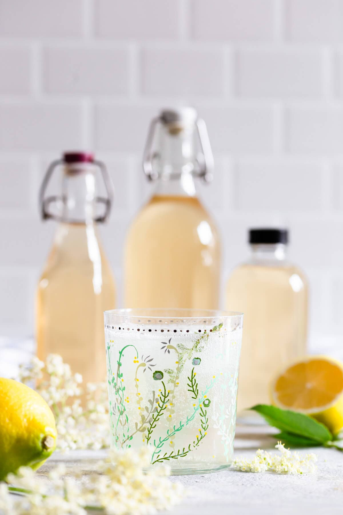 straight ahead view of a glass with fizzy elderflower cordial and cordial bottles at the back