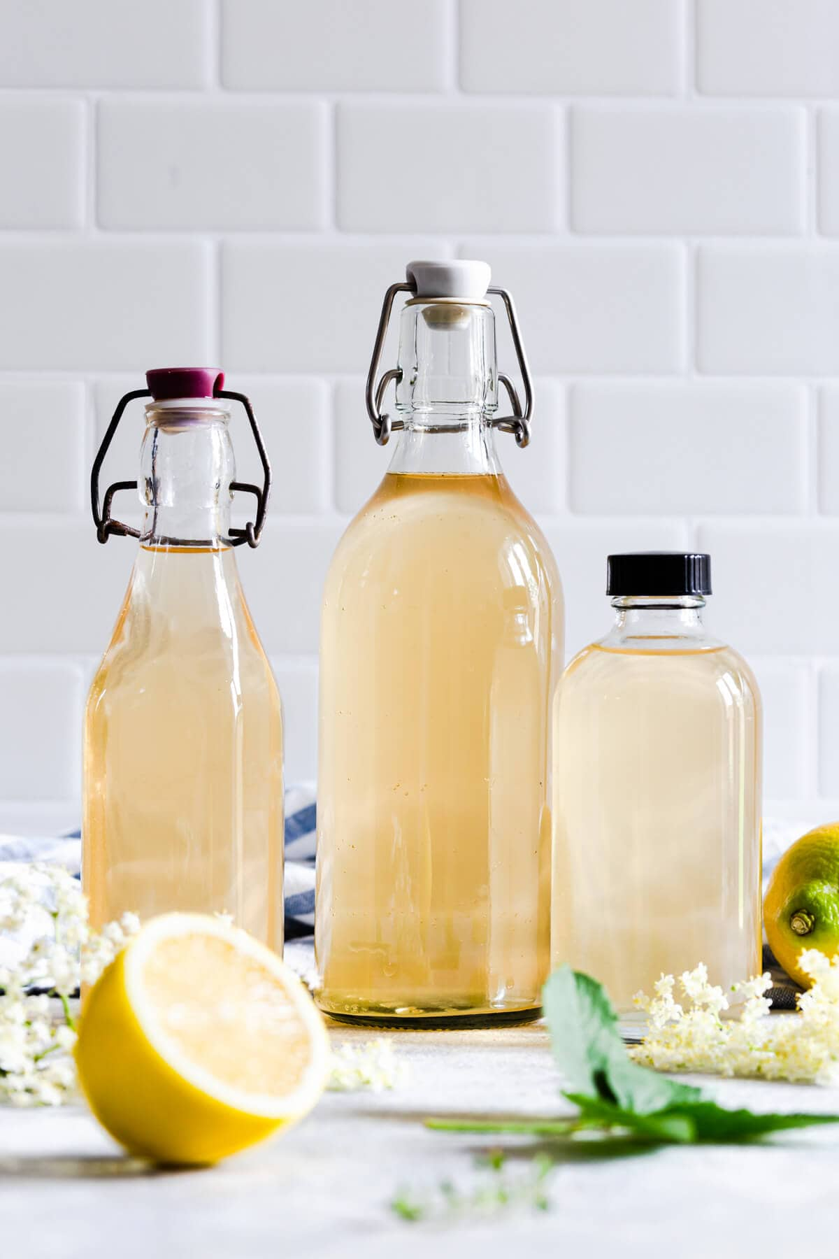 straight ahead view of 3 different glass bottles filled with elderflower cordial