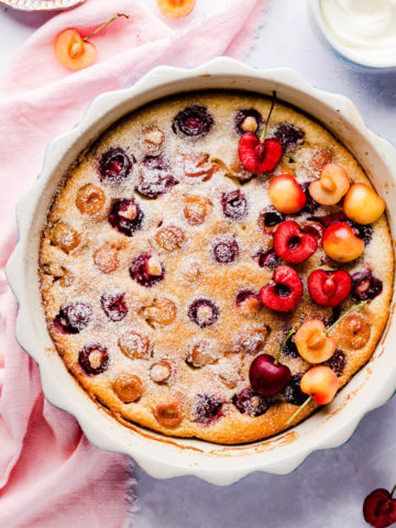 top view of cherry clafoutis in a baking dish and dusted with some icing sugar
