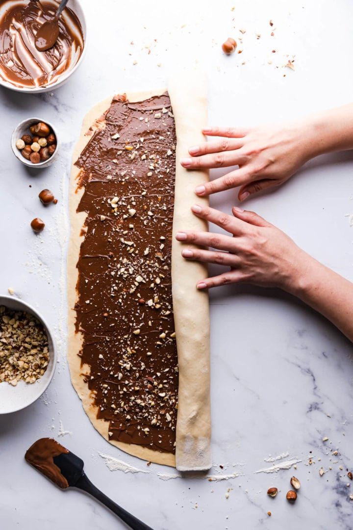 overhead view of a person roling the babka dough into a log
