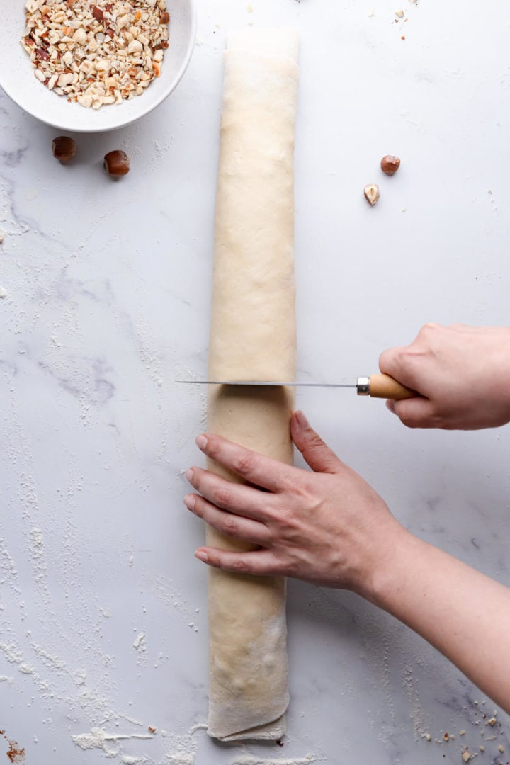 overhead view of rolled dough being sliced in half