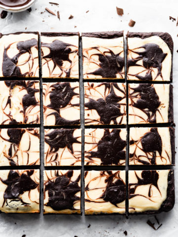 overhead shot of cheesecake topped brownies cut into 12 individual squares