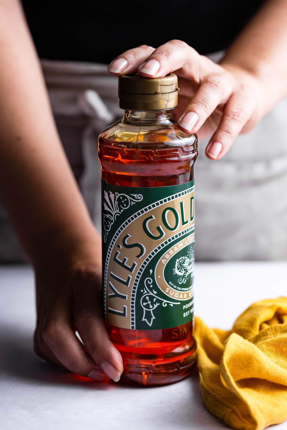 side close up at a person holding a bottle of Lyle's Golden Syrup