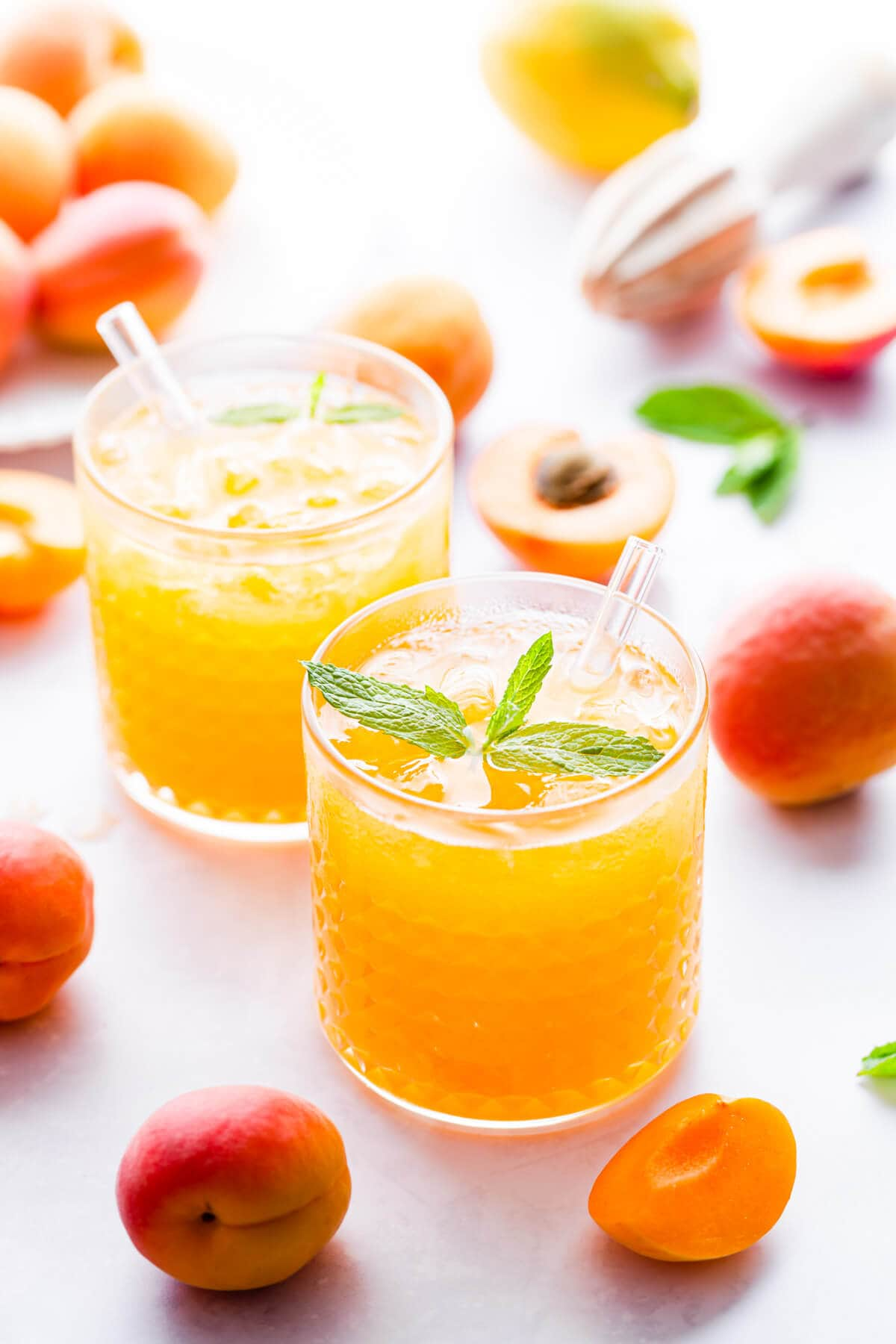 side close up of short tumbler glass filled with crushed ice and apricot nectar
