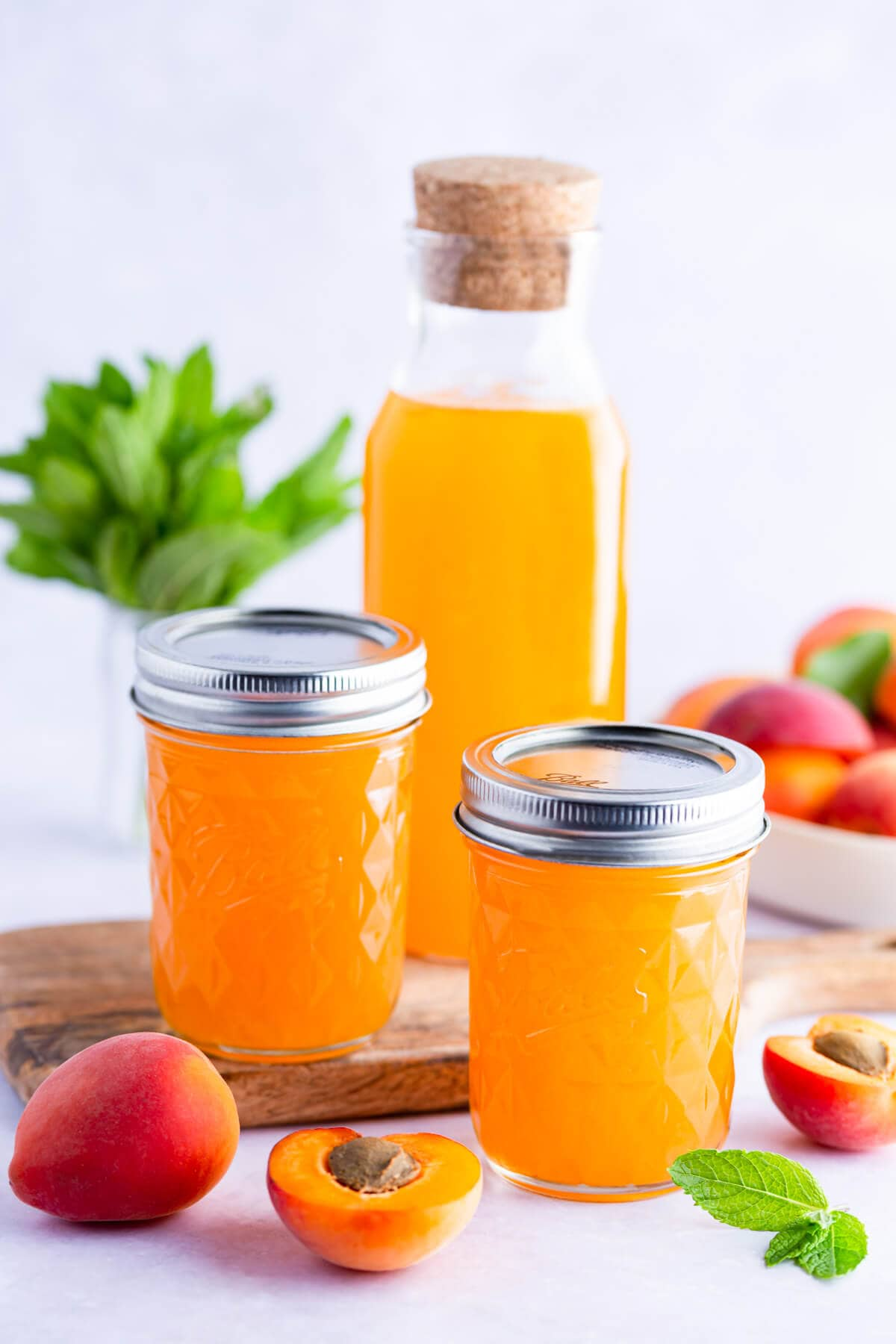 side view of 2 small glass jars and one glass bottle with apricot nectar