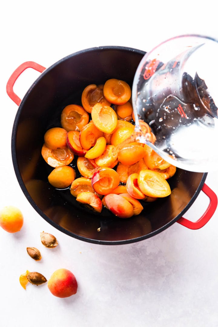 top view of water being added to a large pan with apricots