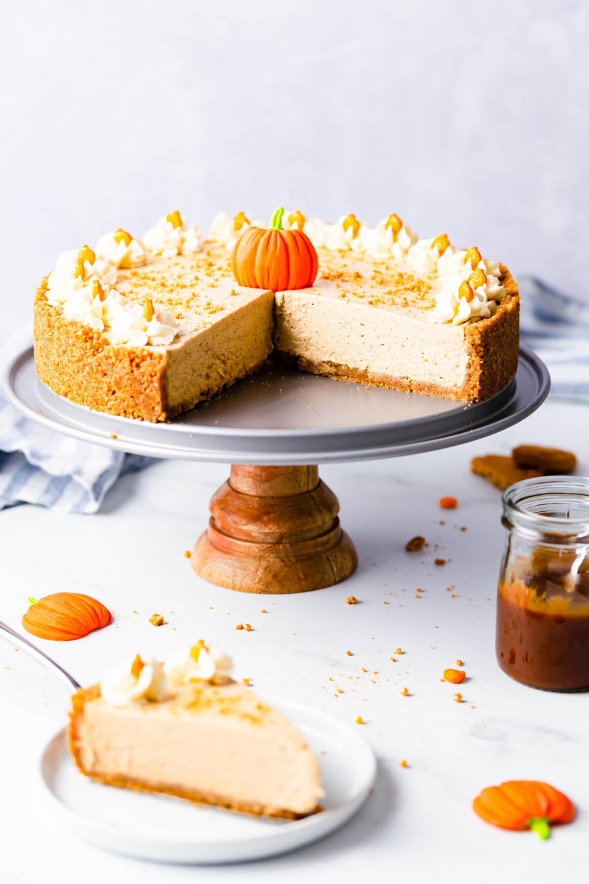 straight ahead angle of a no bake pumpkin cheesecake on a small cake stand with couple of pieces cut out