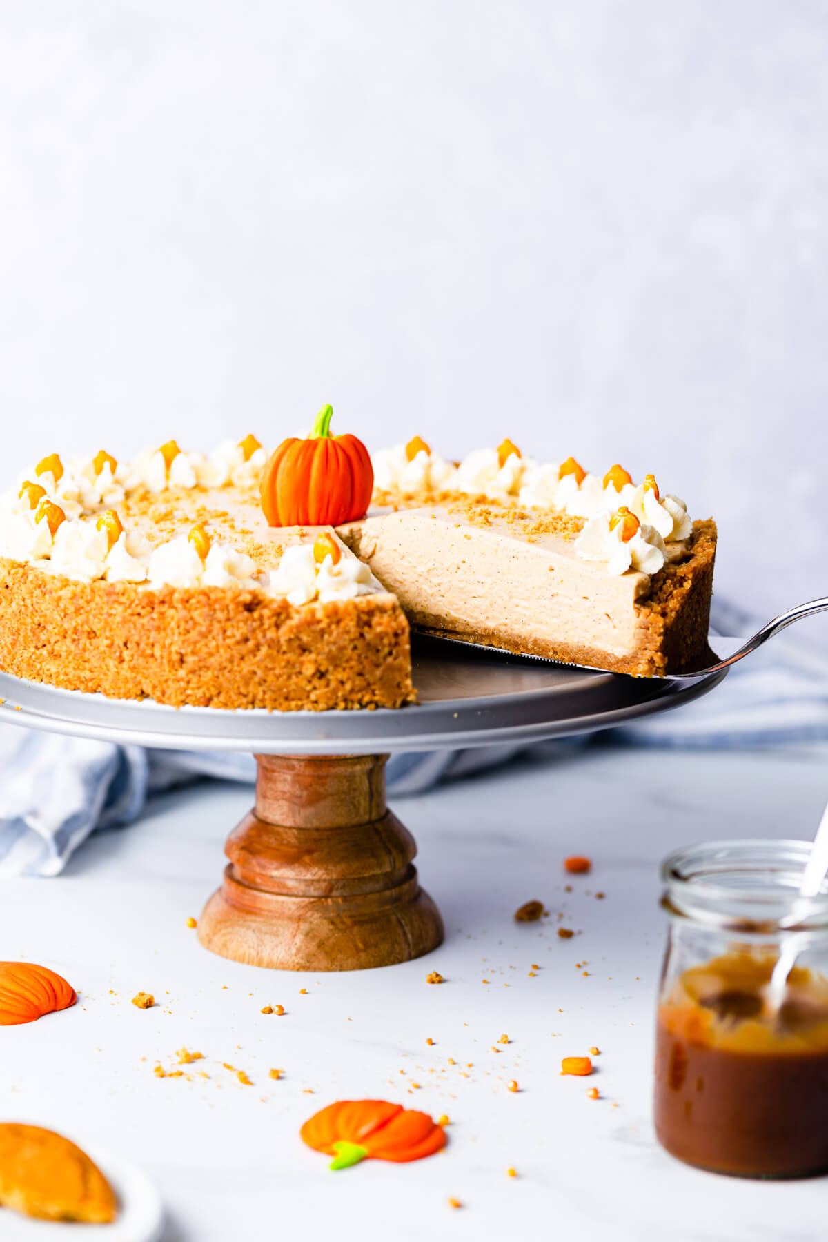 side angle close up at a slice of pumpkin cheesecake being lifted on a cake lifter