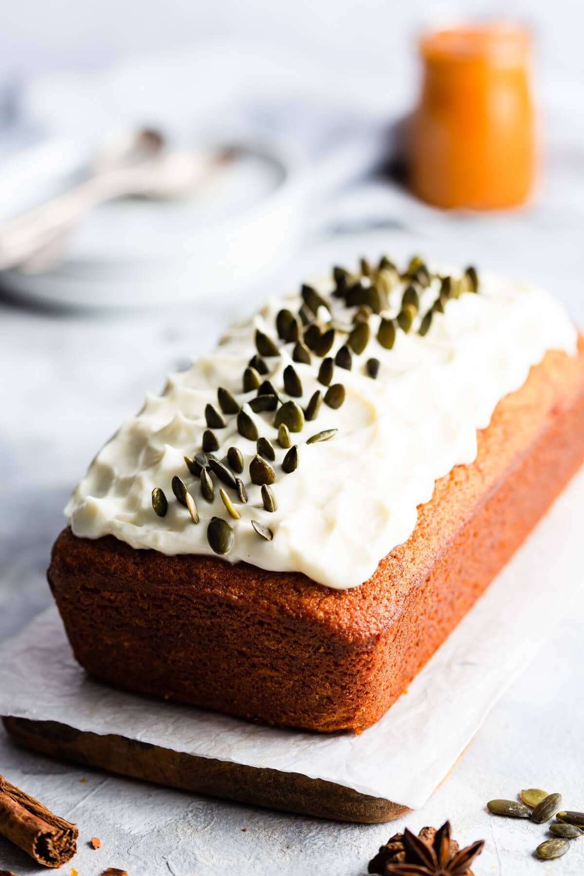side close up at pumpkin loaf cake topped with cream cheese and pumpkin seeds