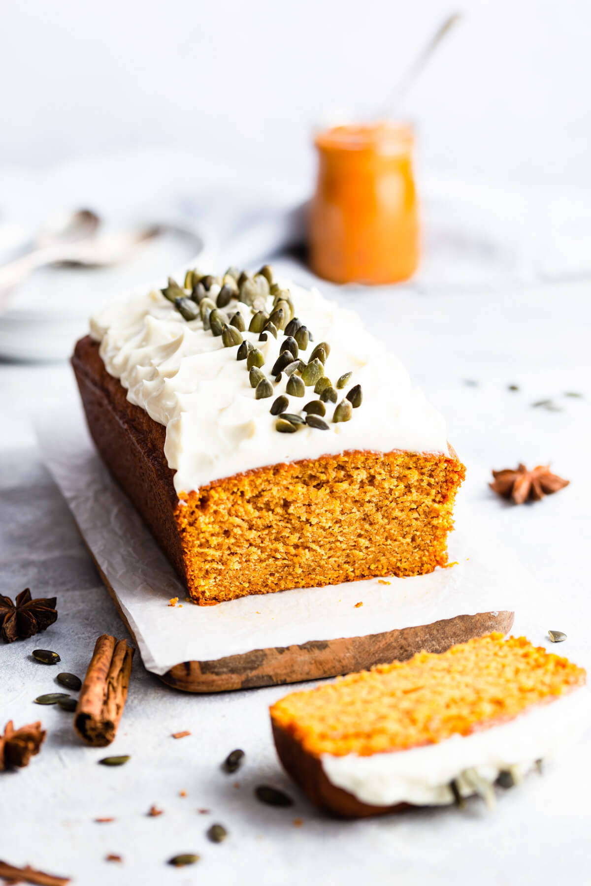 side angle photo of pumpkin loaf with frosting and slice cut off