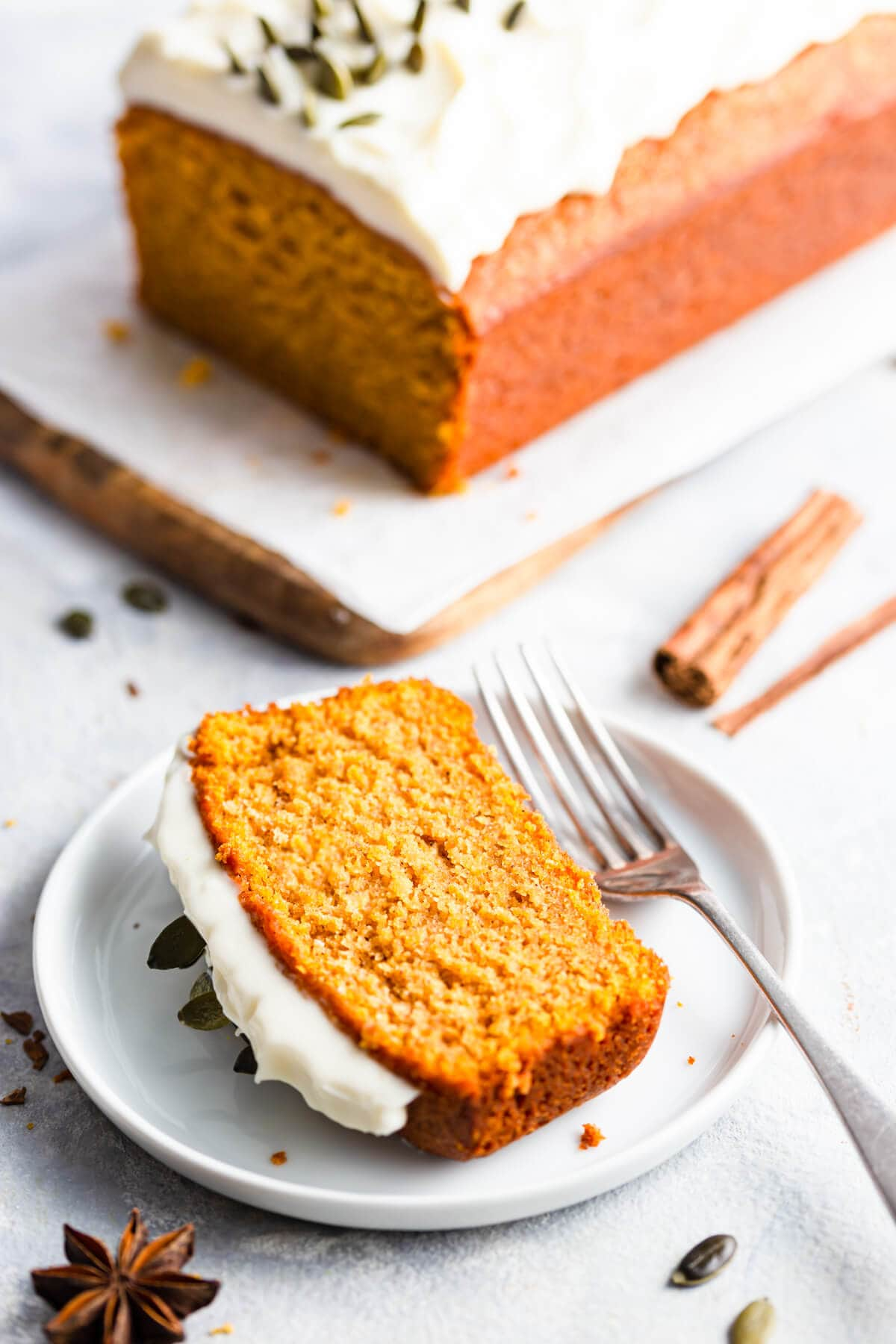 side close up at a slice of pumpkin loaf cake on a small plate