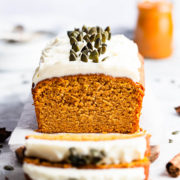 straight ahead close up at pumpkin loaf cake topped with cream cheese and pumpkin seeds