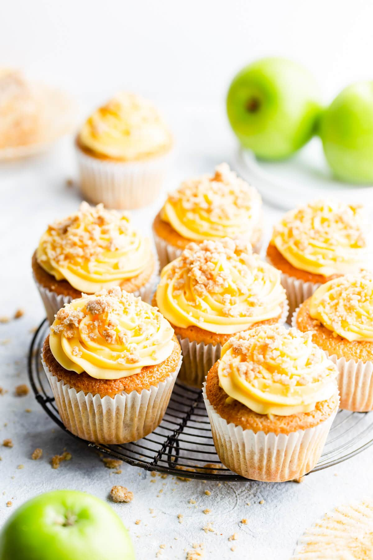 45 degree angle view at apple crumble cupcakes on a round wire rack
