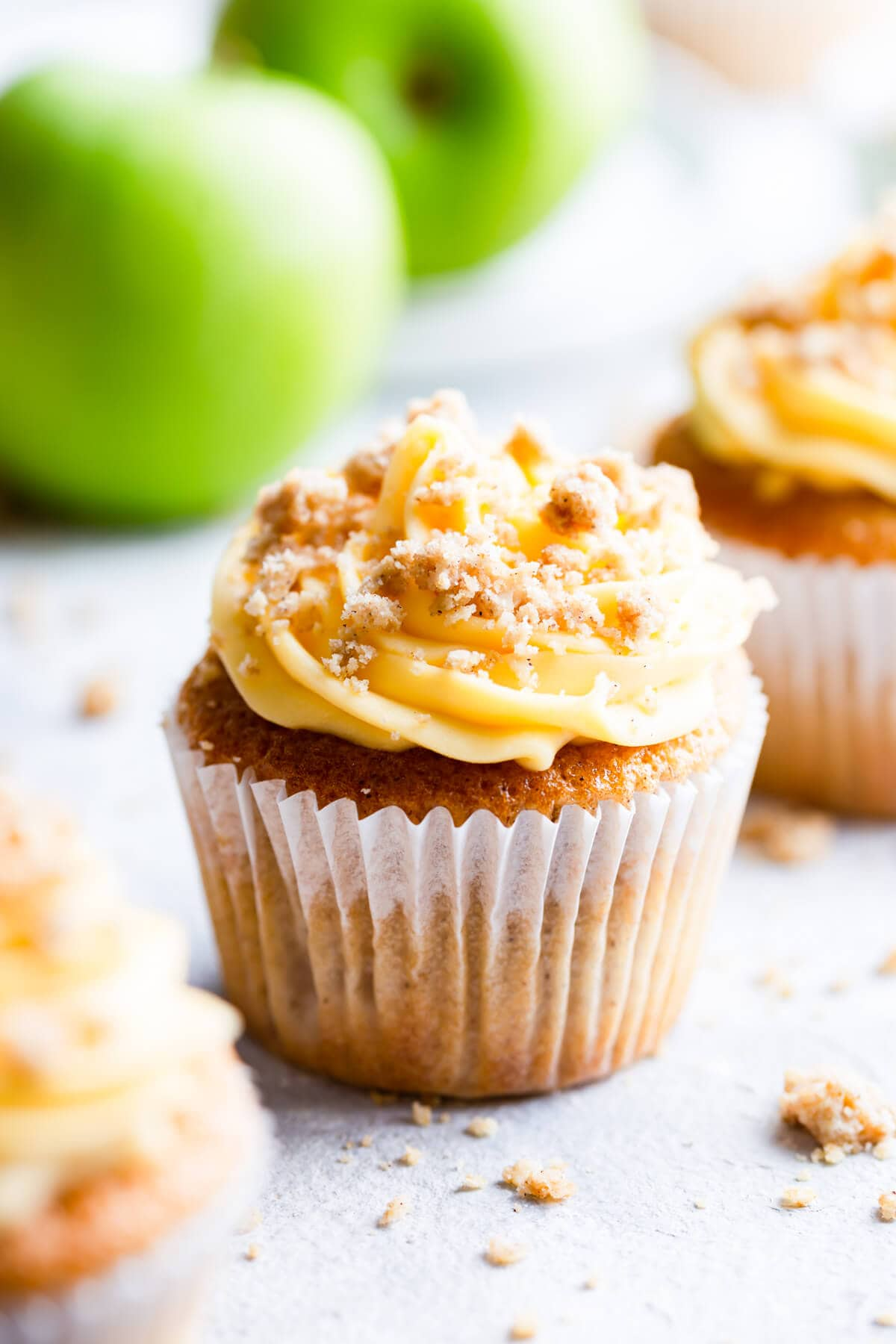 side super close up at an apple crumble cupcake with some green apples in the back