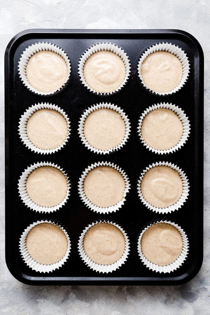 top view of the muffin tin filled with 12 cases with cupcake batter