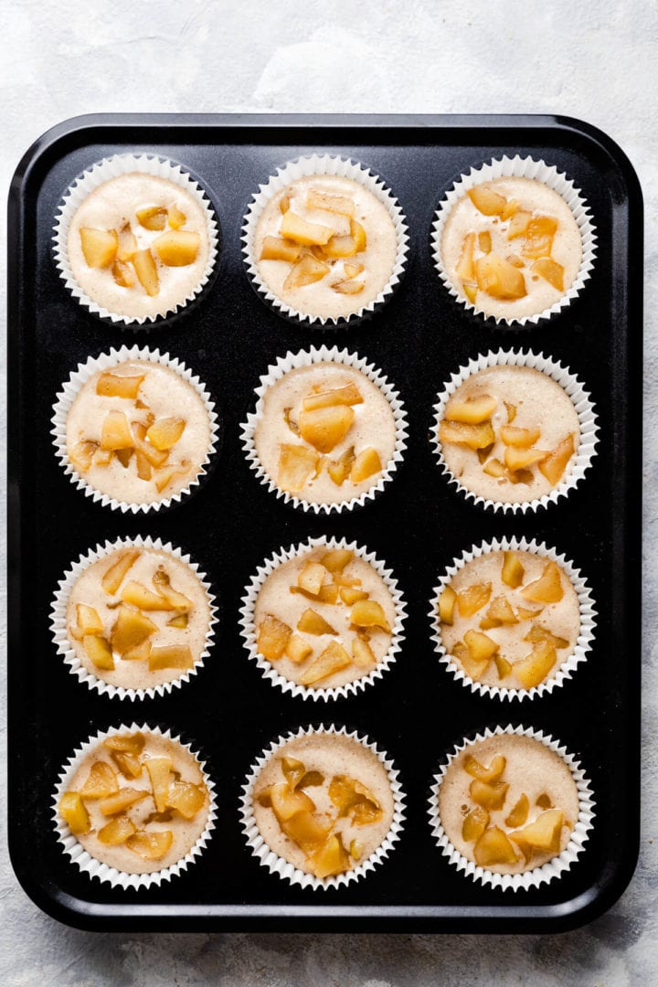 top view of muffin tin filled with cupcakes batter and topped with stewed apples