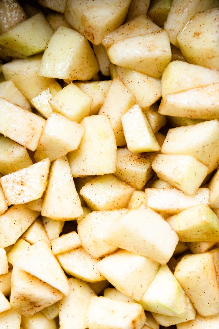 top view close up of chopped apples covered in butter, sugar and cinnamon