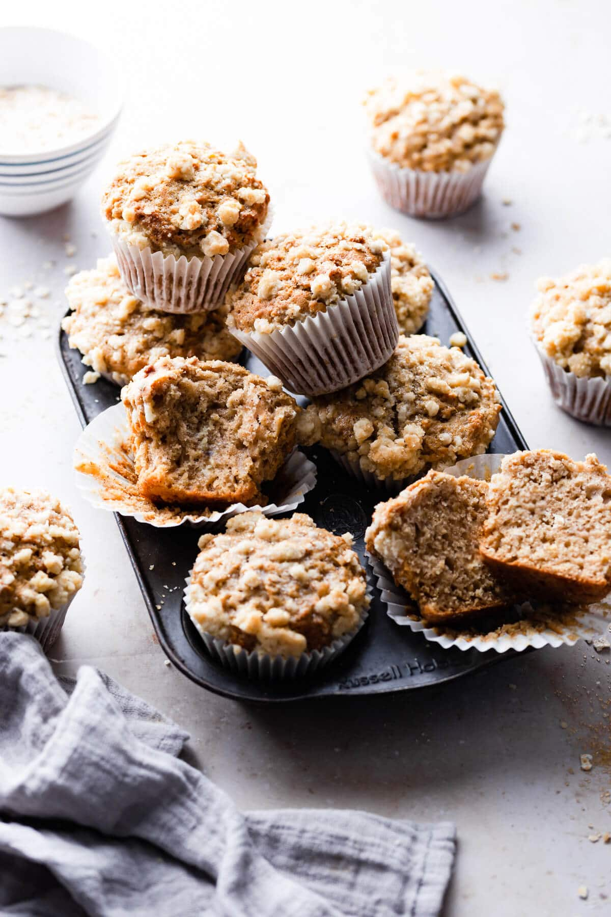 45 degree angle shot of cinnamon oatmeal muffins piled up on a muffin tin
