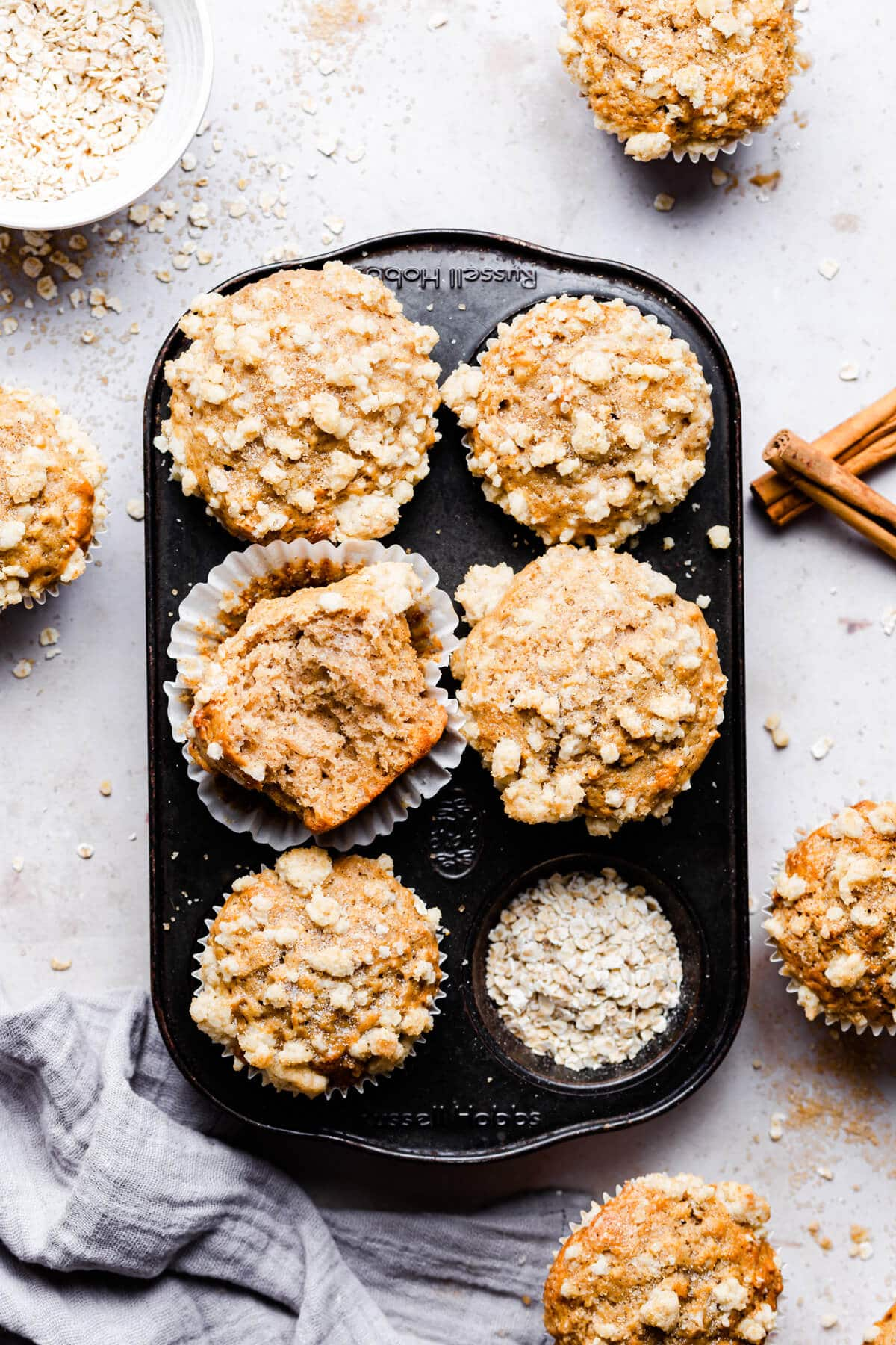 overhead shot of 5 cinnamon muffins in a baking tin with one muffin missing a bite