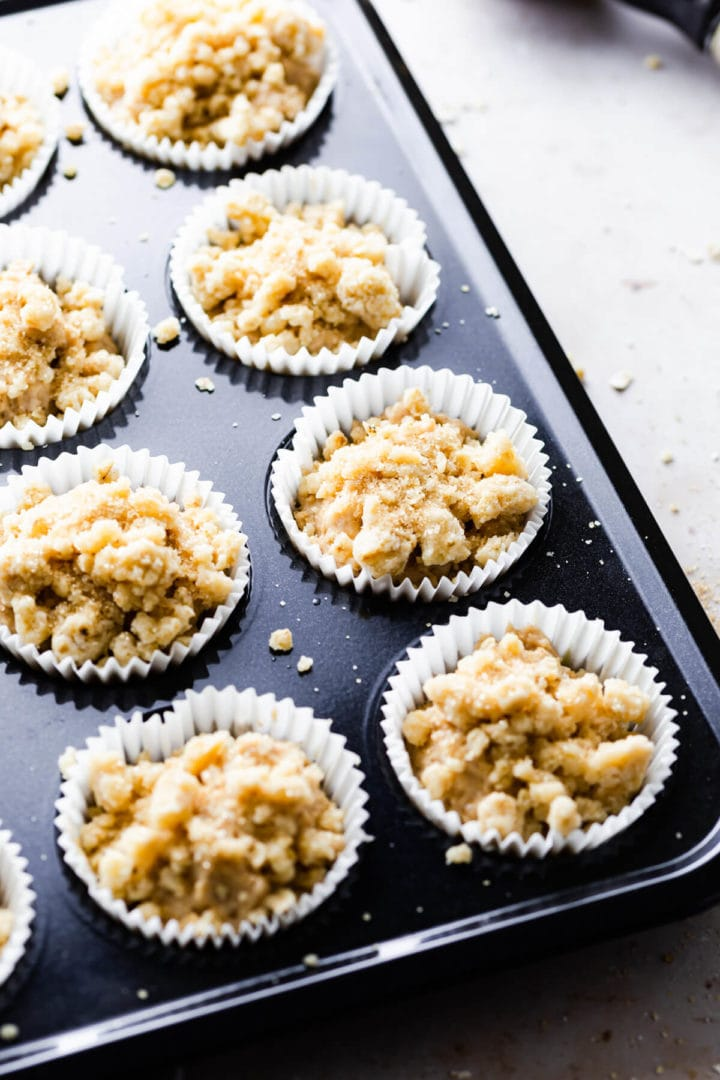 45 degree angle shot of muffin batter in paper cases in muffin tin topped with cinnamon crumble topping