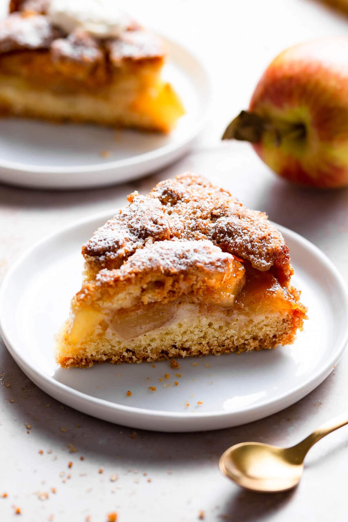 side super close up at an individual slice of an apple cake on a small plate