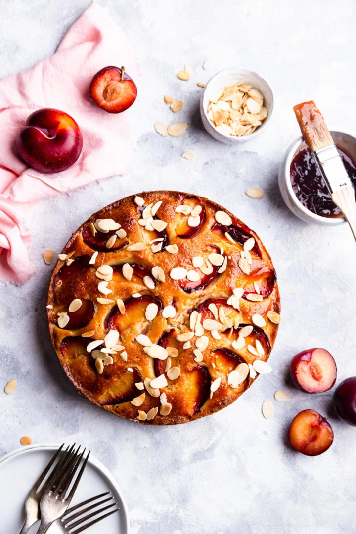 overhead shot of plum cake with flaked almonds on top