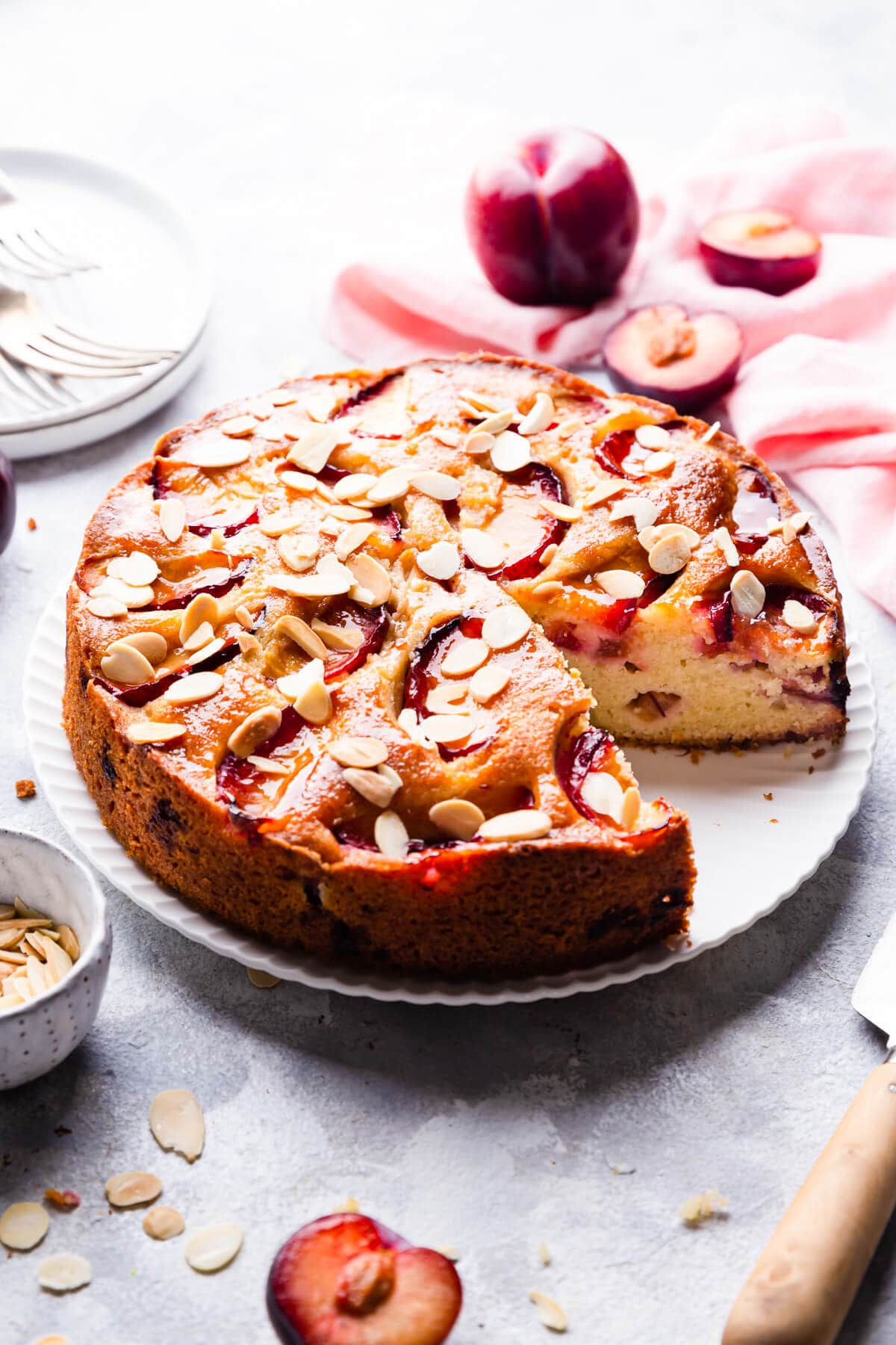 45 degree angle view of plum and almond cake with slice cut out
