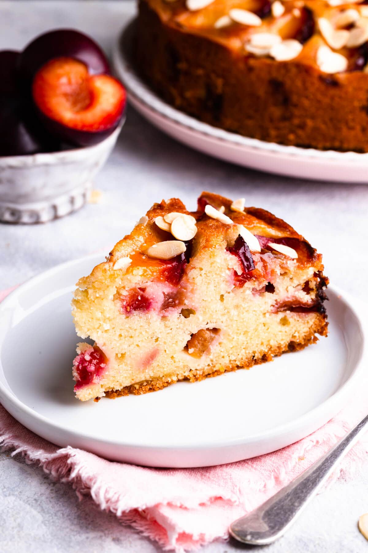 side super close up at one slice of plum and almond cake on a white plate