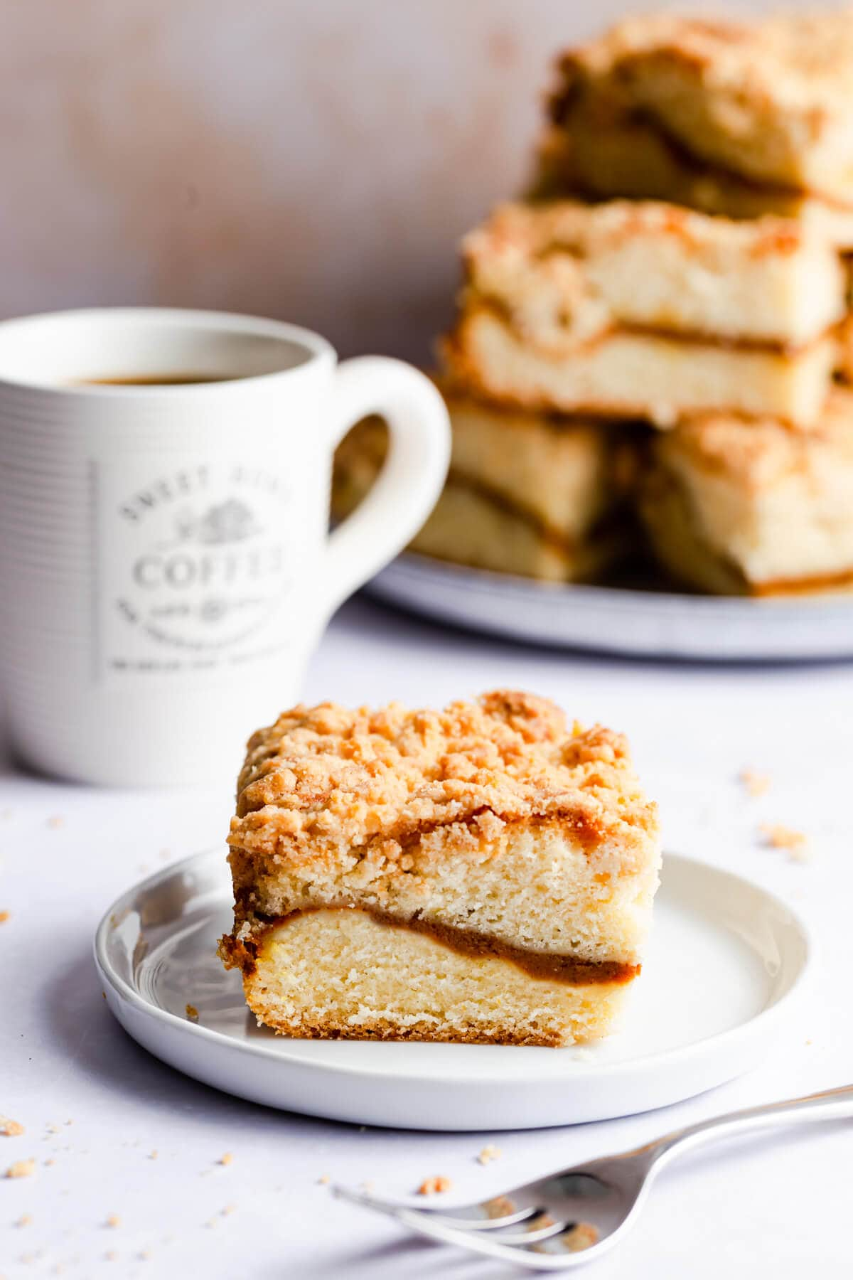 45 degree angle photo of an individual slice of pumpkin coffee cake on a small plate
