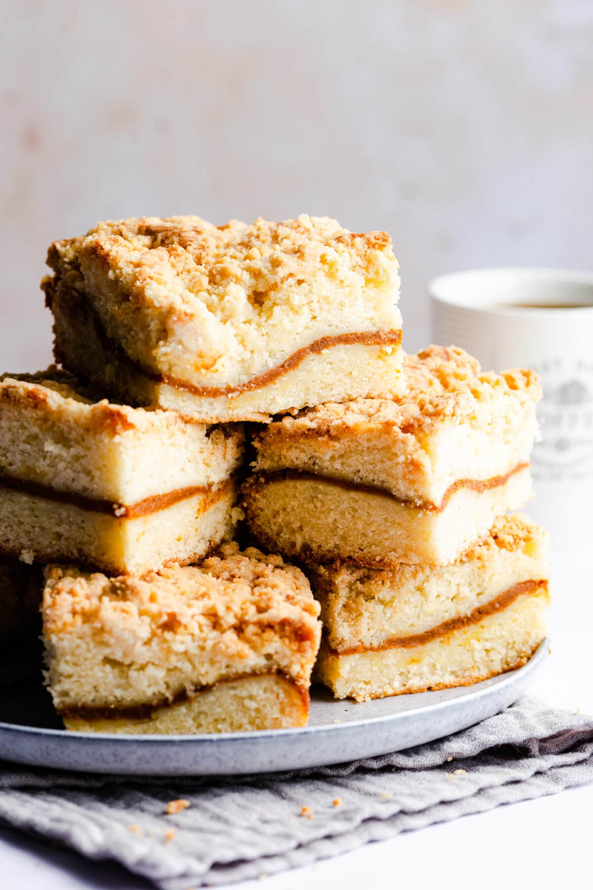side close up at square pieces of coffee cake piled up on a plate
